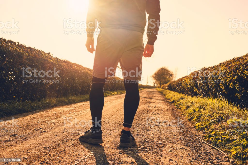 Man stood backlit in golden sunshine on a country road about to start his run. stock photo