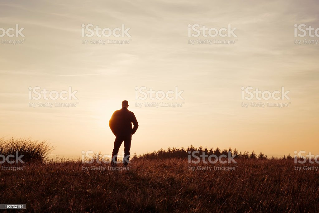 Man stood contemplating in the countryside looking at the sunset stock photo