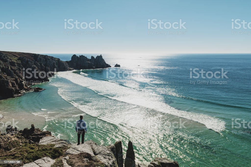 Man stood looking out over Pedn Vounder Beach towards Logan's Rock, Cornwall stock photo