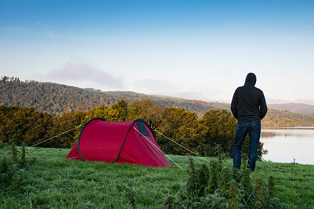 man stood next to a red tent on a hill - tent stock photos and pictures
