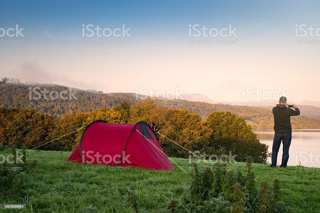 Man stood next to a red tent on a hill stock photo