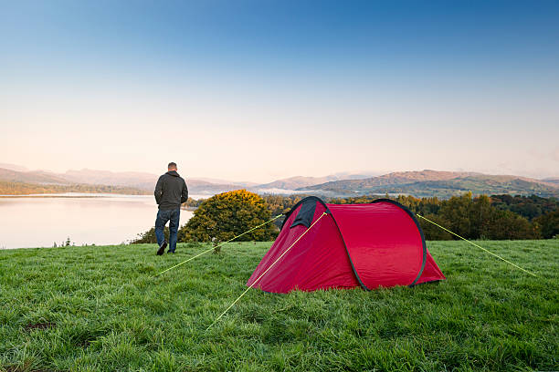 man stood next to a red tent on a hill - tent stock pictures, royalty-free photos & images