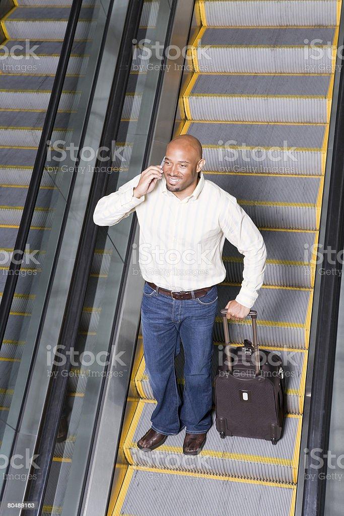 Um homem espera em uma Escada Rolante foto de stock royalty-free