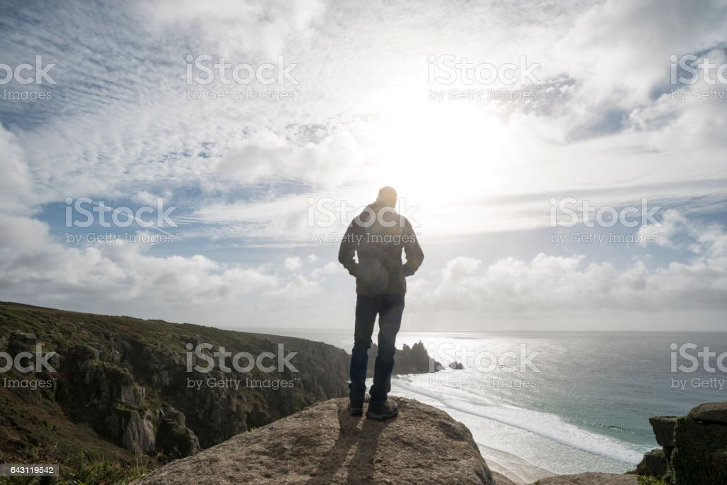 Man stood on cliffs enjoying the view, South Cornwall. stock photo
