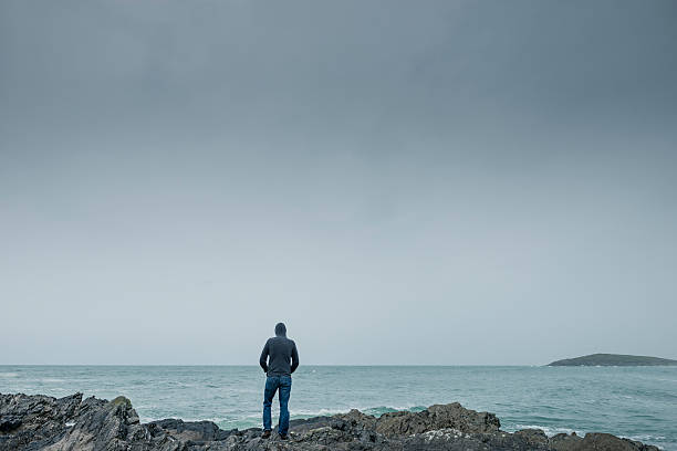 Man stood on rocks on the shoreline in gloomy weather. - foto de acervo