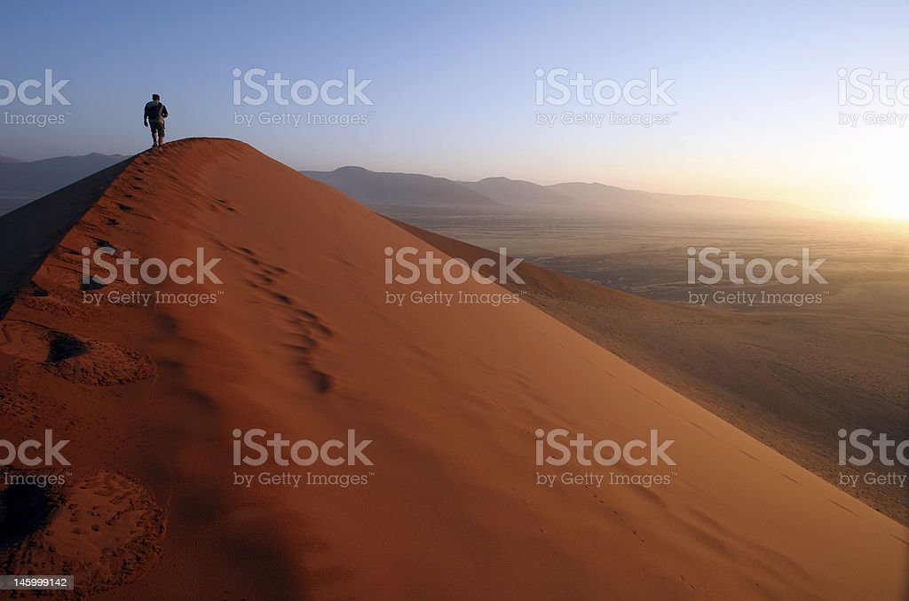 Man stood on top of a sand dune at sunset stock photo