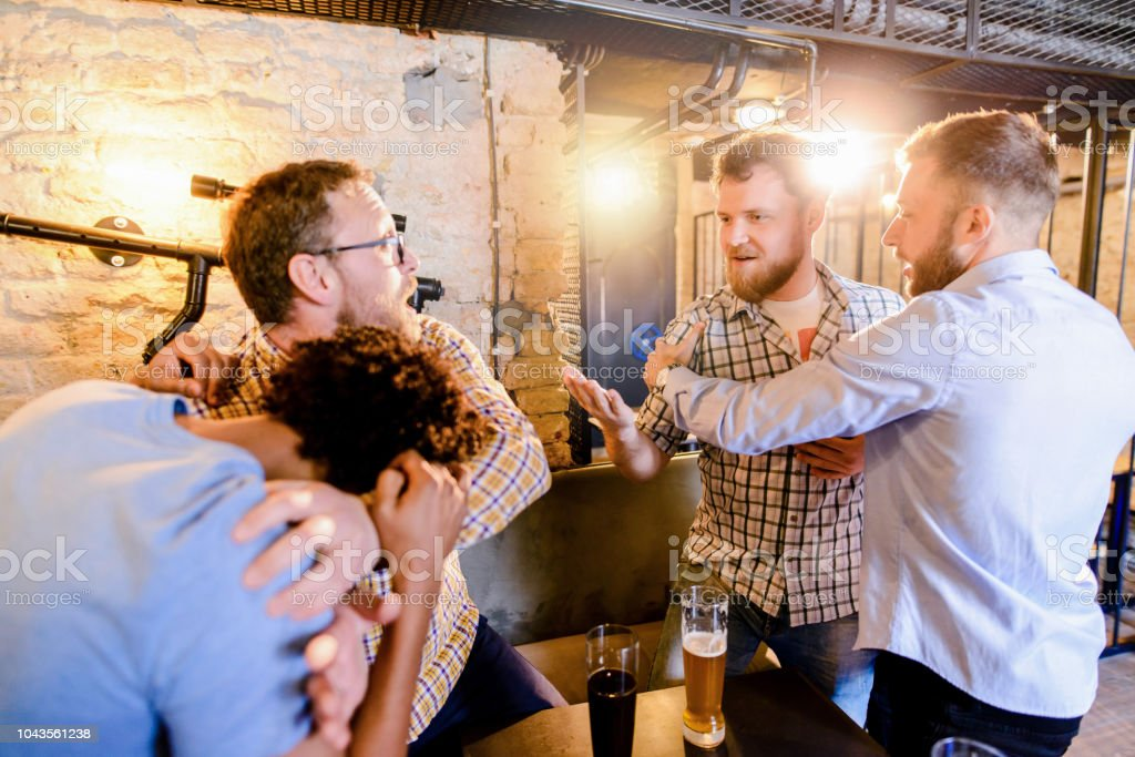 Man stopping his friend to get in a bar fight. Group of man drinking in a bar and fighting. stock photo