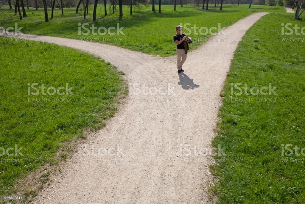 Man stops at trail fork, checks direction, spring, Piedmont, Italy stock photo