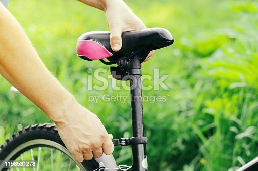 istock A man straightens, repairs the seat of a mountain bike on a forest road. Bicycle breakdown, vehicle repair. 1156531273