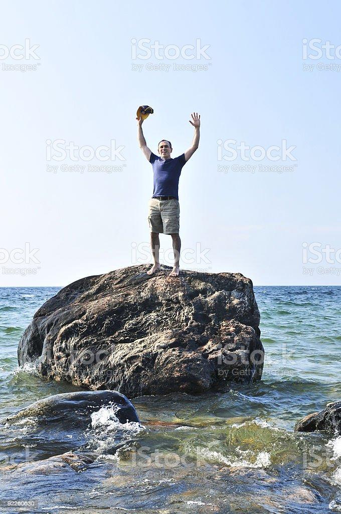 Man stranded on a rock in ocean royalty-free stock photo