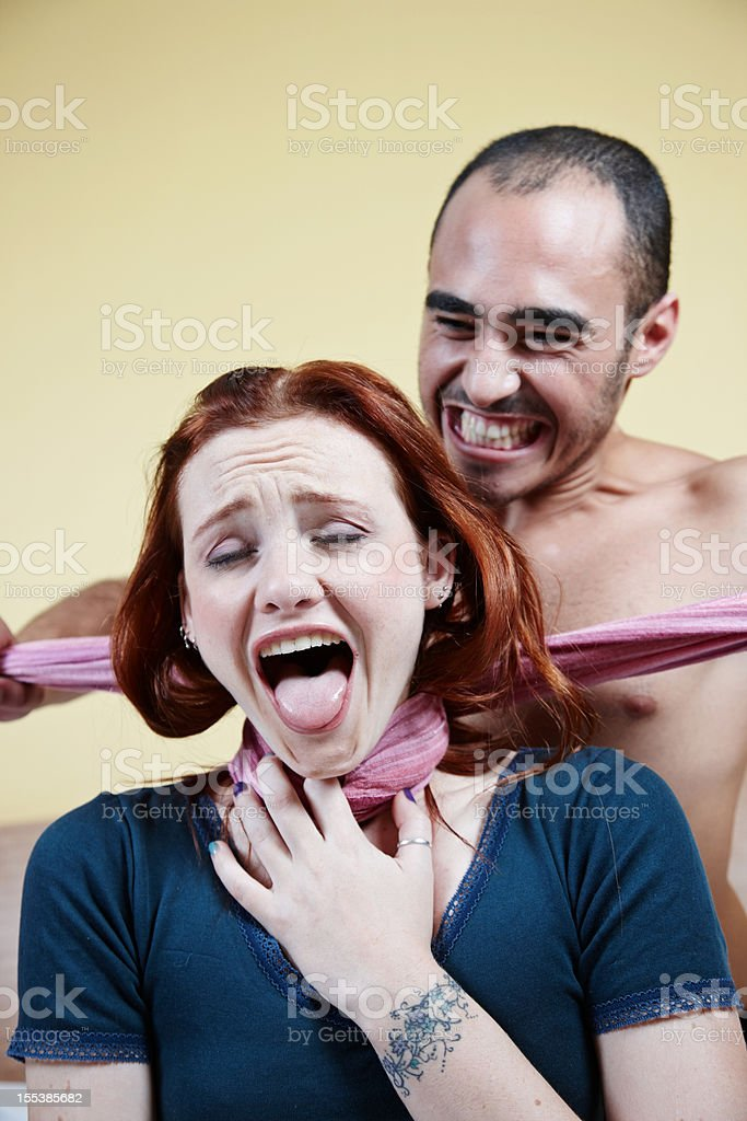 Man strangling woman with scarf on bed stock photo