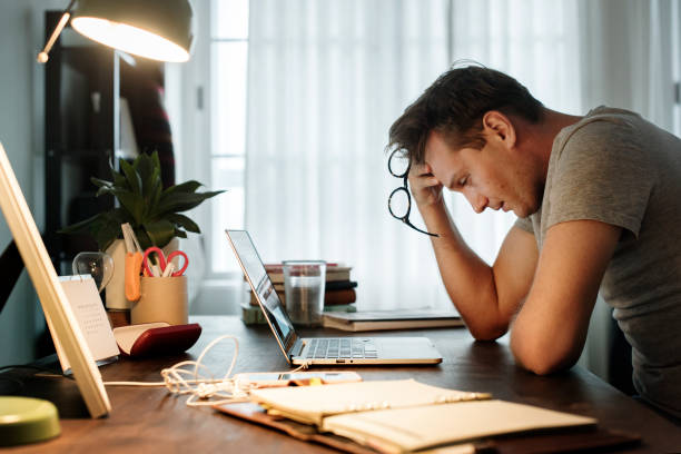 Man stressed while working on laptop stock photo