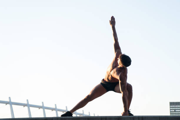 Man stretching hands and legs on roof stock photo
