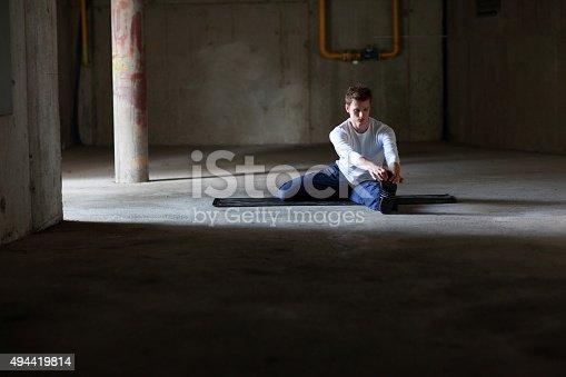 511849865istockphoto man stretching on dark parking lot 494419814