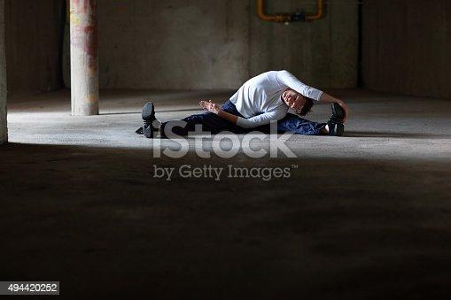 511849865istockphoto man stretching on dark parking lot 494420252