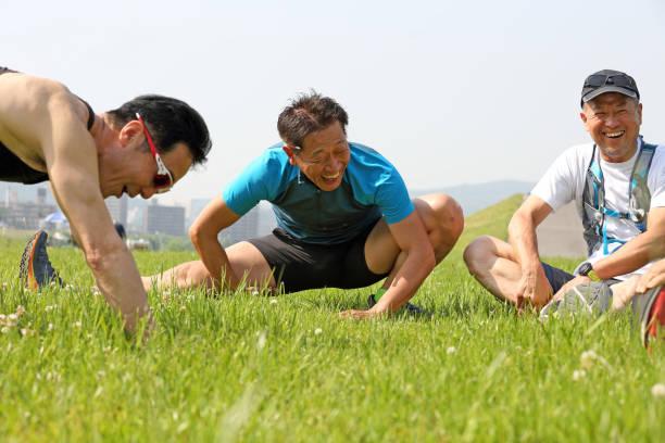 Man stretching on grass stock photo