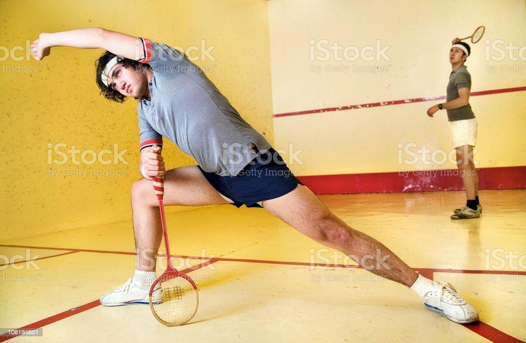 Man Stretching on Squash Court Holding Racket stock photo