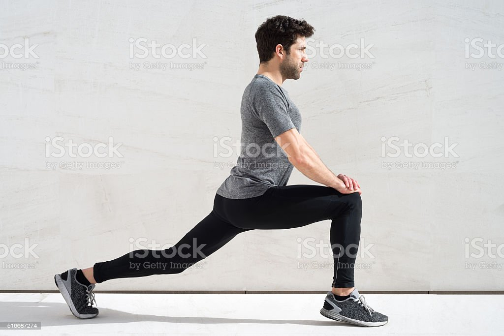 Man stretching quadriceps stock photo
