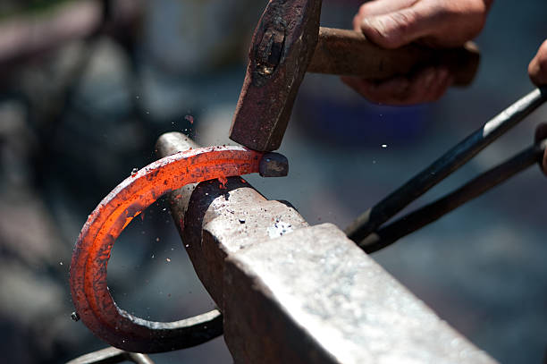 a man striking a red hot horseshoe on the anvil - hovslagare bildbanksfoton och bilder
