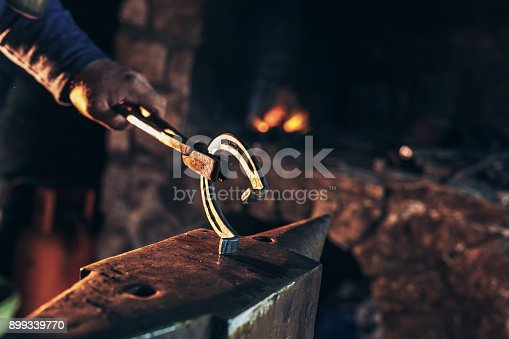 1130936245istockphoto A man striking horseshoe on the anvil 899339770