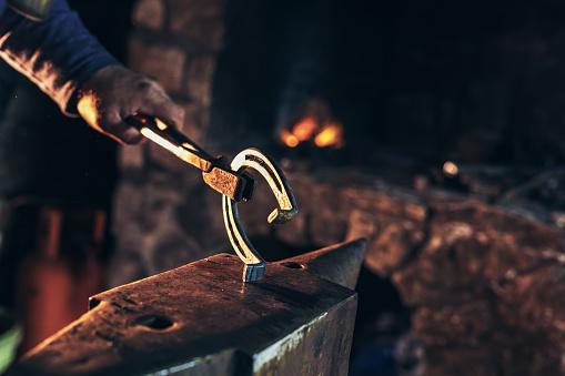 1130936245 istock photo A man striking horseshoe on the anvil 899339770