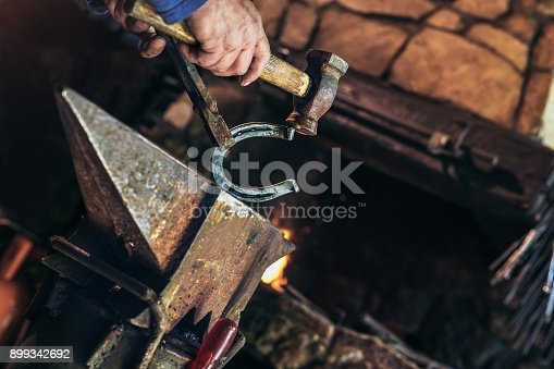 1130936245istockphoto A man striking horseshoe on the anvil 899342692