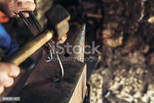 1130936245istockphoto A man striking horseshoe on the anvil 936381452