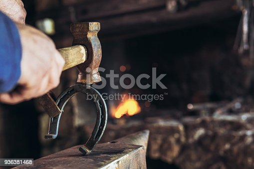 1130936245istockphoto A man striking horseshoe on the anvil 936381468