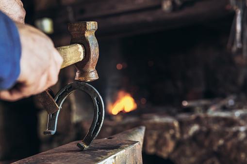 1130936245 istock photo A man striking horseshoe on the anvil 936381468