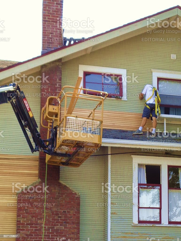 Man stripping paint from heritage home stock photo
