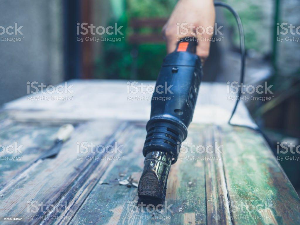 Man stripping paint with heat gun stock photo