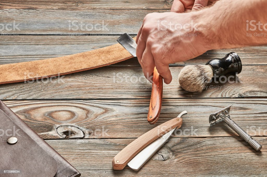 Man stropping straight razor with leather tool stock photo