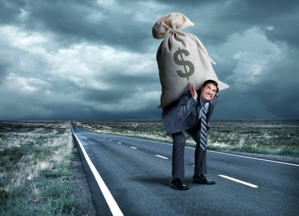 Man Struggles To Carry Money Bag On His Back stock photo