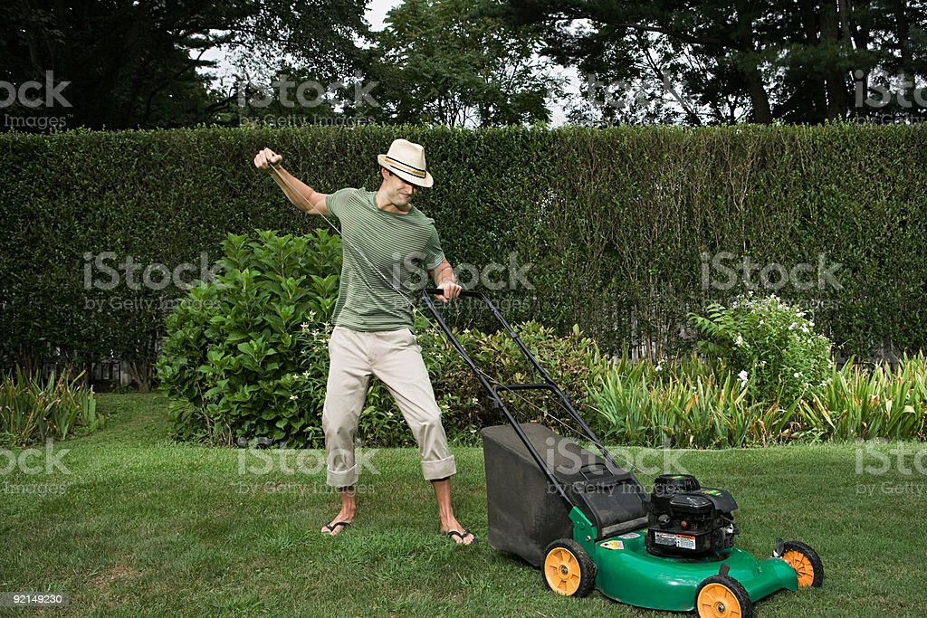 Man struggling with a lawn mower stock photo