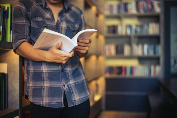 man studentin liest ein buch in einer bibliothek, junge mann öffnen und lesen ein buch, hautnah, warmen retro-ton. - geführtes lesen stock-fotos und bilder