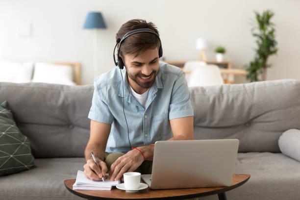 hombre estudiar audio escucha haciendo algunas notas - online learning fotografías e imágenes de stock