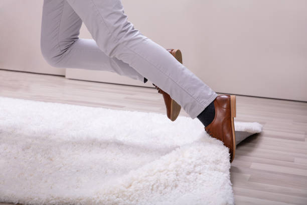 Man Stumble In A Carpet Near Ladder stock photo
