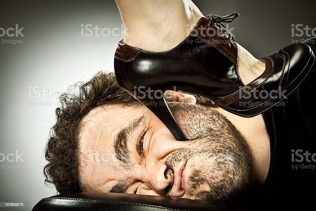 man submission with woman high heel shoe stock photo