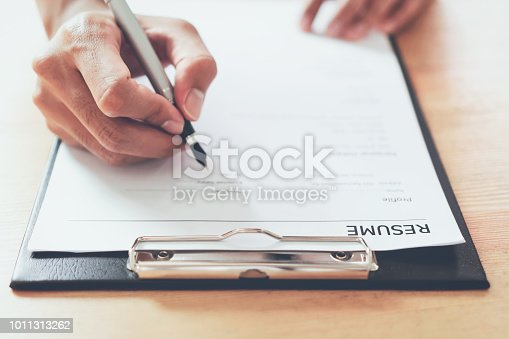 istock man submit resume to employer to review job application. The concept presents the ability for the company to agree with the position of the job. 1011313262