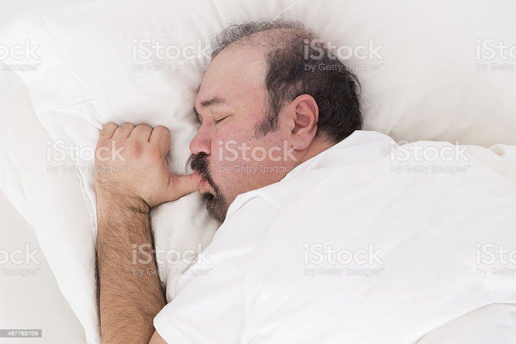 Man sucking his thumb while sleeping stock photo