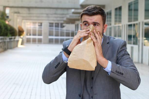 Homem que sofre um cheiro desagradável no trabalho - foto de acervo