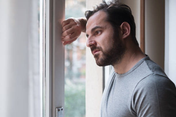 Man suffering and feeling alone at home stock photo