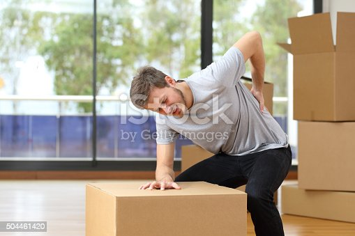 istock Man suffering back ache moving boxes 504461420
