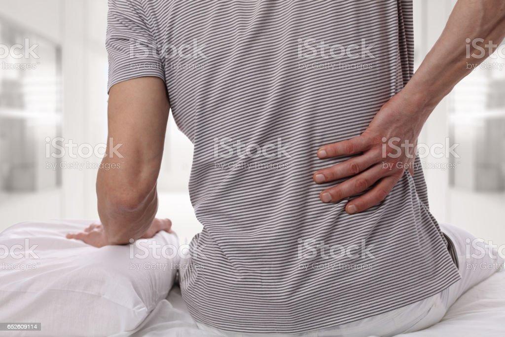 Adam evde yatak odasında sırt ağrısı muzdarip. Rahat yatak ve yastık nedenleri sırt ağrısı. stok fotoğrafı