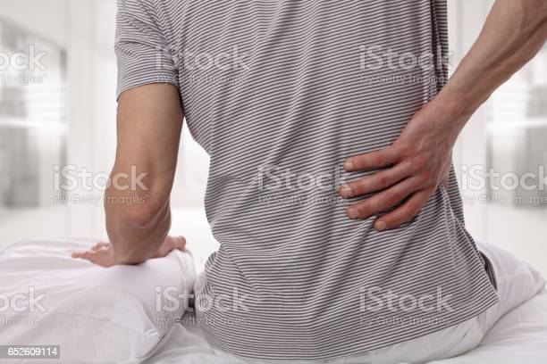 Man Suffering From Back Pain At Home In The Bedroom Uncomfortable Mattress And Pillow Causes Back Pain Stock Photo - Download Image Now