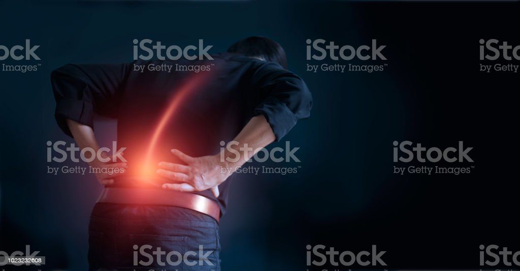Man suffering from back pain cause of office syndrome, his hands touching on lower back. Medical and heath care concept stock photo
