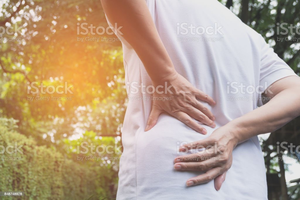 A man suffering from backache, spinal injury and muscle issue problem at outdoor. stock photo