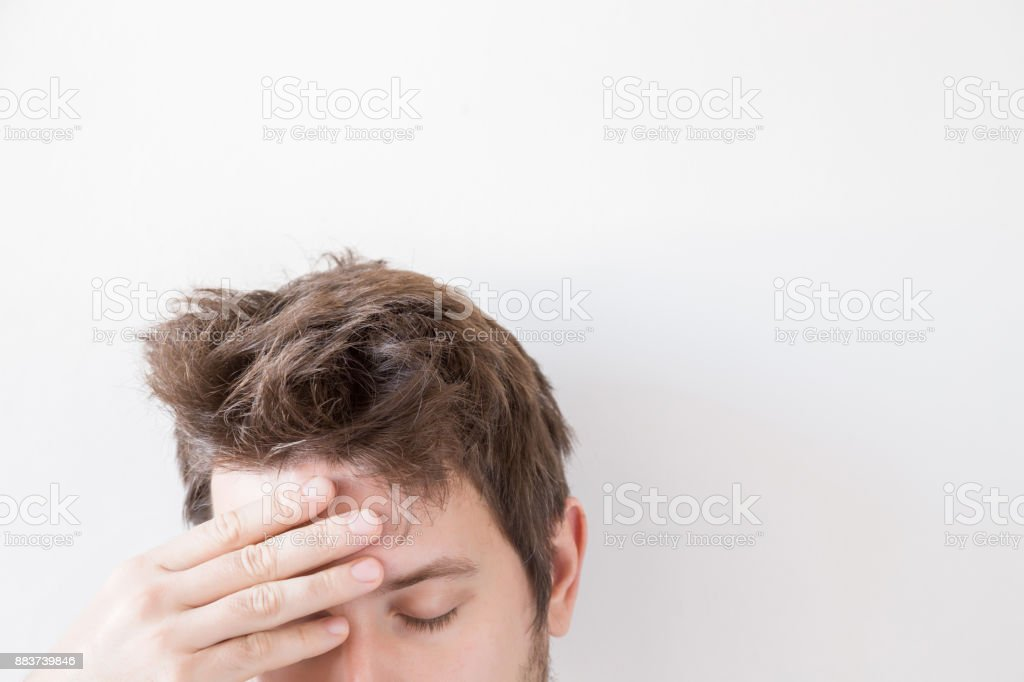 Man suffering from daily headache and touching his forehead with hand. Problem concept. Empty place for a text or object on the gray background. stock photo