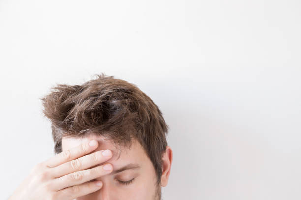 man suffering from daily headache and touching his forehead with hand. problem concept. empty place for a text or object on the gray background. - head injury stock photos and pictures