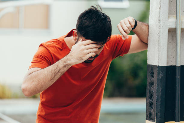 man suffering from dizziness with difficulty standing up while leaning on wall - condizione medica foto e immagini stock